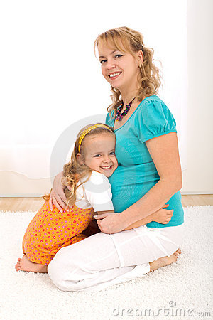 Happy little girl with beautiful pregnant woman