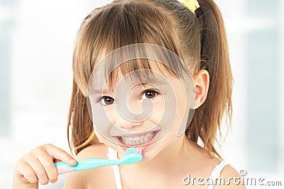 Happy little girl brushing her teeth Stock Photo