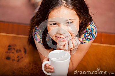 Happy little girl drinking tea
