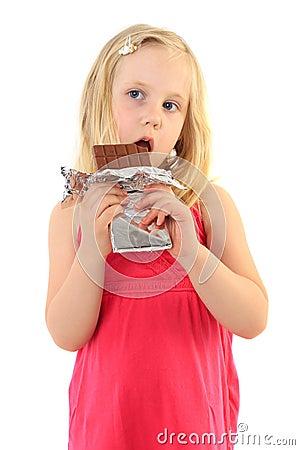 Happy little girl eating chocolate