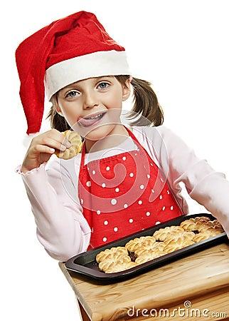 Happy little girl eating Christmas cookies