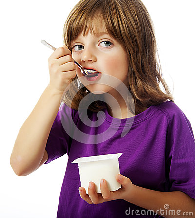 A happy little girl eating a yogurt