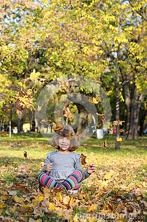 Happy little girl fun with autumn leaves