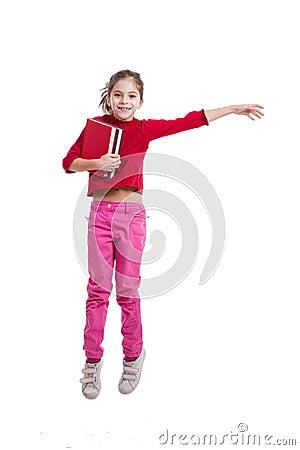 Happy little  girl holding books jumping