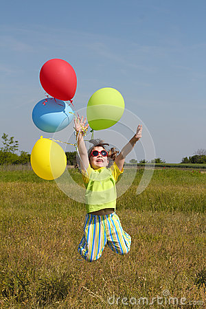 Happy little girl jumping with balloons