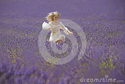 Happy little girl jumps in field of lavender