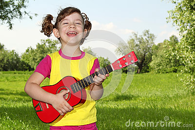 Happy little girl play guitar
