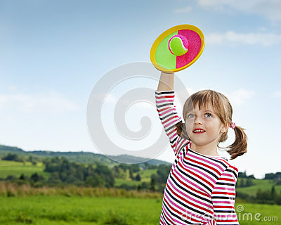Happy little girl playing with a ball
