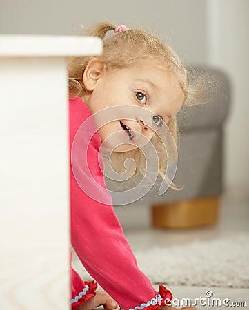 Happy little girl playing peek-a-boo