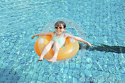Happy little girl relaxing and swimming in the pool Stock Photo