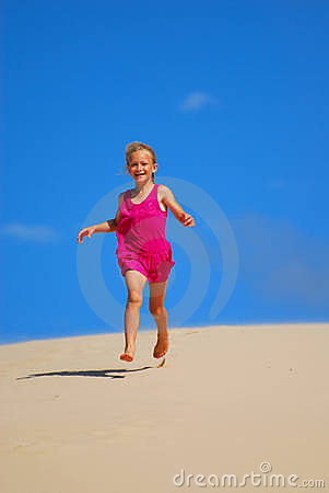 Happy little girl running down sand dunes