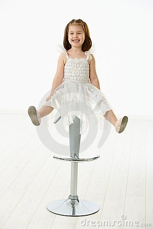 Happy little girl sitting on chair