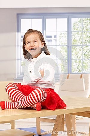 Happy little girl sitting on top of table