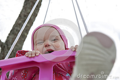 Happy little girl in a swing