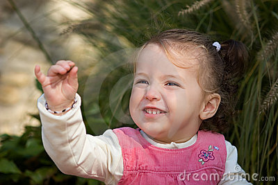 Happy little girl toddler excitedly showing off a pebble.