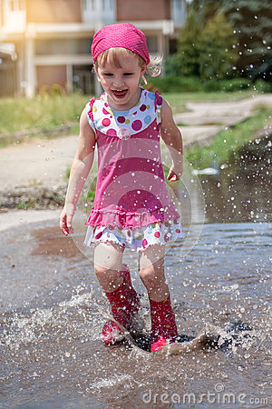 Free Happy Little Girl Wearing Pink Rain Boots Jumping Into A Puddle. Royalty Free Stock Photography - 55533917