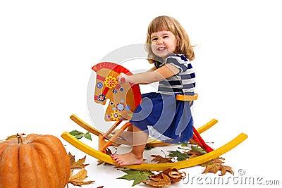 Happy little girl on wooden horse