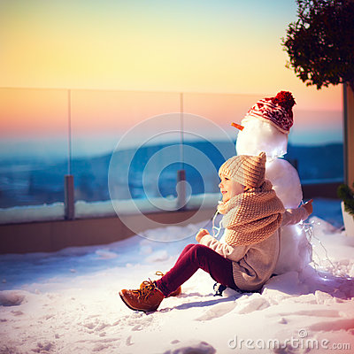 Free Happy Little Kid And His Friend Snowman Watching The Sun Goes Down Sitting In Snow On Rooftop Terrace In One Winter Evening Stock Photo - 84312810