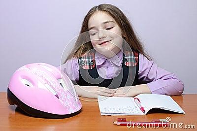 Happy little school girl doing homeworks at desk