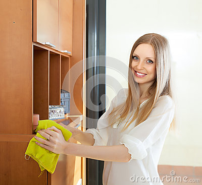 Happy  long-haired woman wiping the dust from furniture
