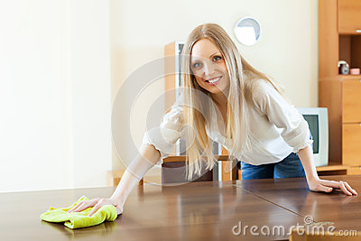 Happy  long-haired woman wiping the   table