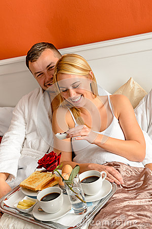 Happy lovers lying bed eating romantic breakfast