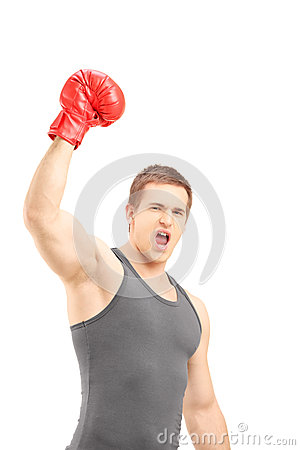 Happy male boxer wearing red boxing gloves and gesturing triumph