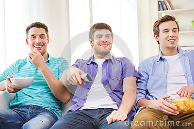 Happy male friends watching tv at home
