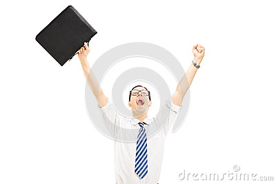 Happy male holding a suitcase and gesturing happiness with raise