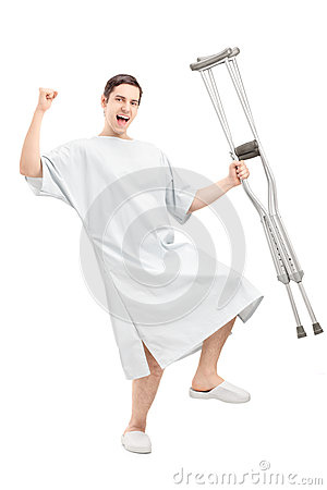Happy male patient in hospital gown holding crutches