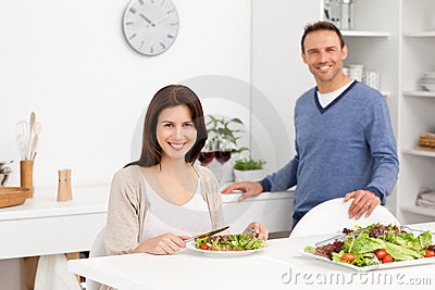 Happy man binging glasses of red wine to his wife