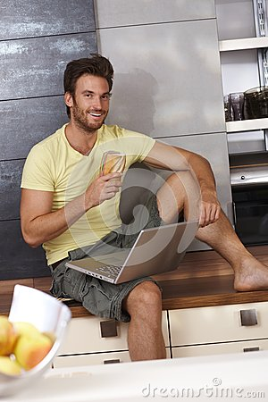 Happy man browsing internet in kitchen