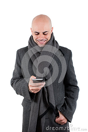 Happy man with coat and scarf using his smart phone.