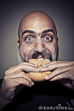 Happy man eating a sandwich