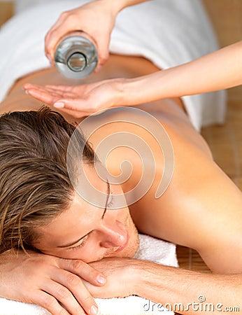 Happy man getting oil massage at spa