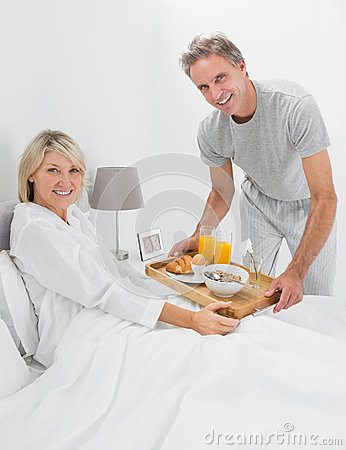 Happy man giving breakfast in bed to his partner