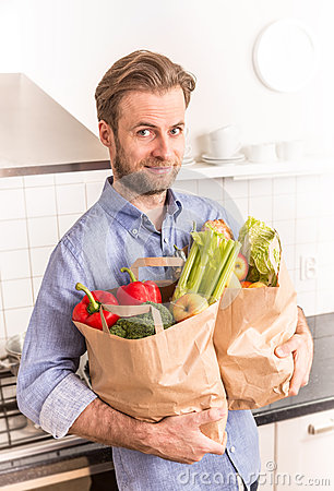 Free Happy Man Holding Paper Grocery Shopping Bag In The Kitchen Royalty Free Stock Image - 69364866