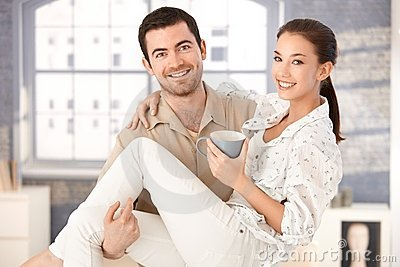 Happy man holding woman in his arms smiling