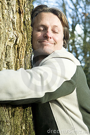 Happy man hugging tree