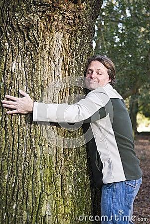 Happy man hugging tree