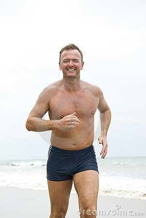 Happy man jogging on beach.