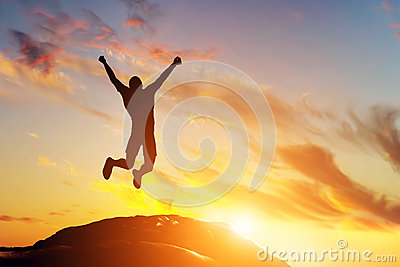 Happy man jumping for joy on the peak of the mountain at sunset. Success Stock Photo