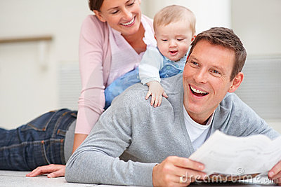 Happy man lying on the floor with baby on his back