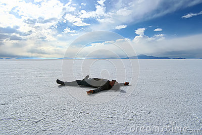 Happy man lying on the surface of Salar de Uyuni,