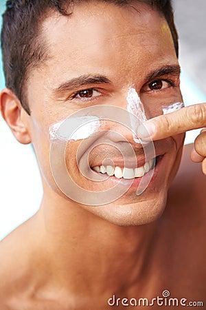 Happy man putting suntan lotion on face