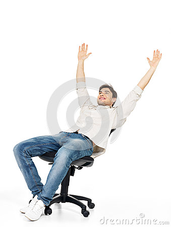 Happy man sits on the chair and raised hands up