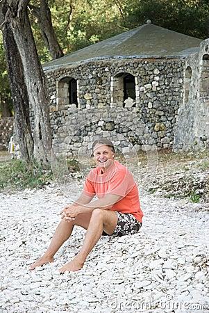 Happy man sitting on beach