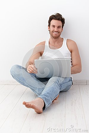 Happy man sitting on floor with laptop
