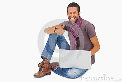 Happy man sitting on floor using laptop giving thumbs up