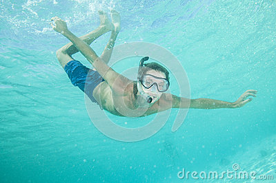 Happy man with snorkel and mask in ocean